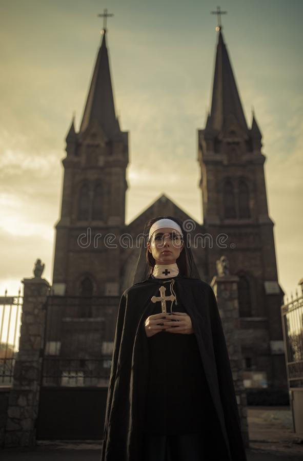 Young nun is standing with cross in her hands on temple background. stock photos
