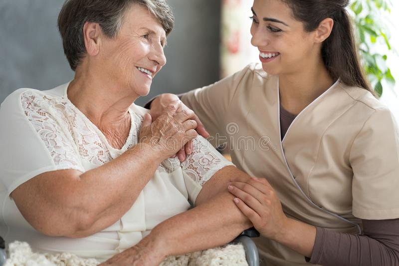 Spending time in retirement home. Young nurse in beige uniform and elder lady spending an afternoon together in a retirement home royalty free stock images