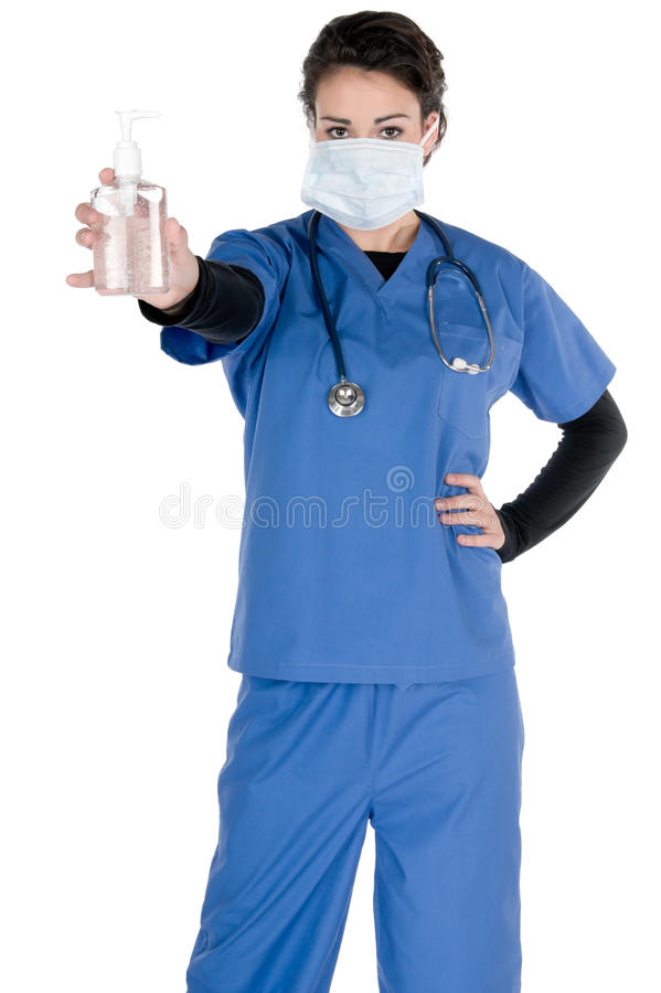 Young nurse, blue scrubs, mask, hand sanitizer. Young female nurse, wearing blue scrubs, a mask on her face and a stethoscope around her neck, offering hand stock images