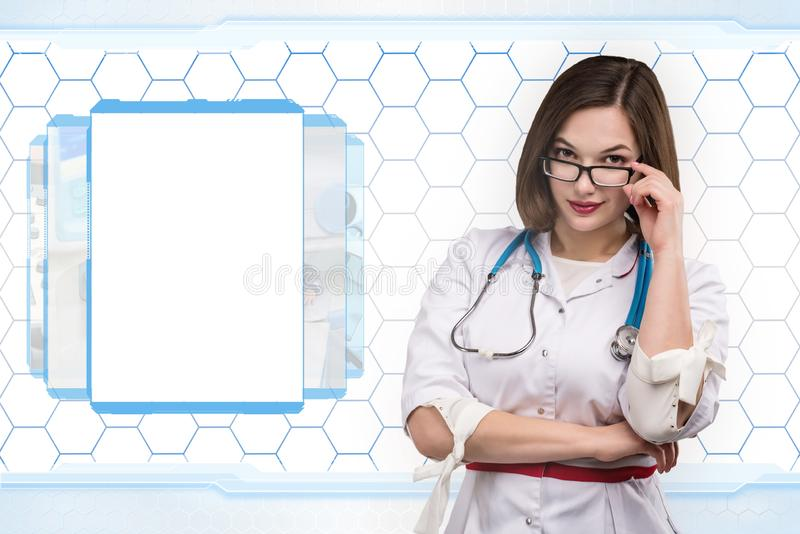 Young nurse or brunette doctor in white coat with stethoscope on hi-tech back stock photo