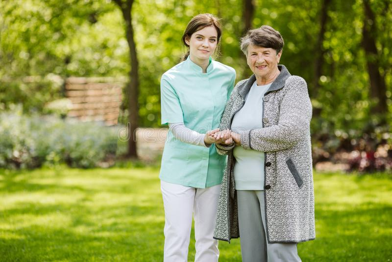 Nurse with elder woman in the garden. Young nurse with elder women in the garden stock photography