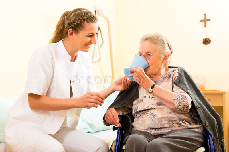 Young nurse and female senior in nursing home. The old lady sitting in a wheel chair royalty free stock images