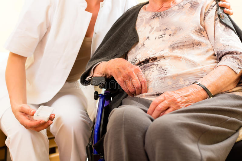Young nurse and female senior in nursing home stock photography