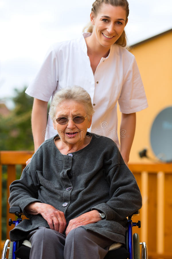 Young nurse and female senior in a wheel chair. Going for a walk royalty free stock photo