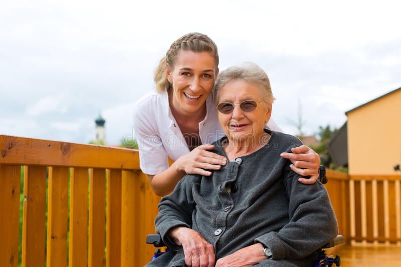 Young nurse and female senior in a wheel chair. Going for a walk stock photos