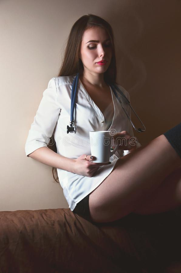 Young nurse girl sitting with coffee cup stock images
