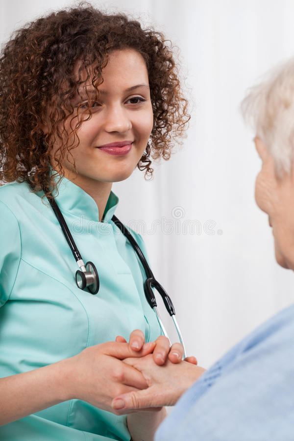 Young nurse holding a woman's hand older stock images