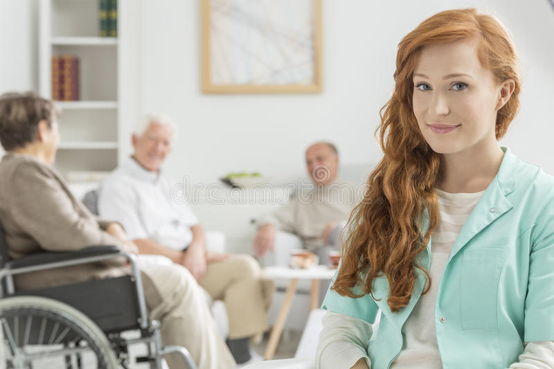 Young nurse at retirement home. Young and red-haired nurse at retirement home stock photos