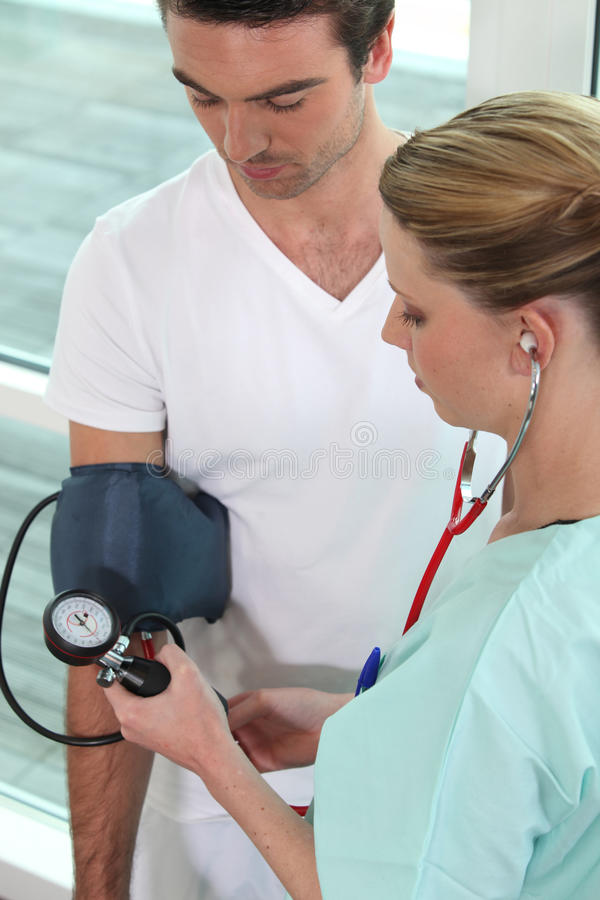 Download Young Nurse Taking Blood Pressure Stock Photo - Image: 24496278
