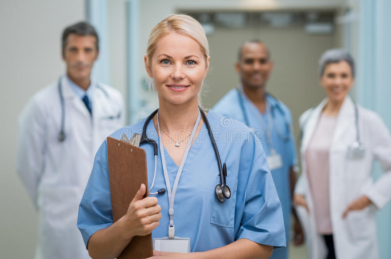 Young nurse and teamwork. Portrait of a smiling young nurse holding clipboard at hospital. Satisfied female nurse outside operation theatre holding clipboard