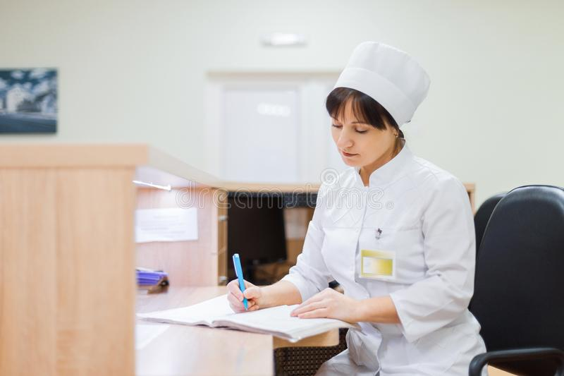 A young nurse in white clothes is sitting at a desk at the reception desk in a private clinic and writing something in a notebook. Woman doctor records stock photos