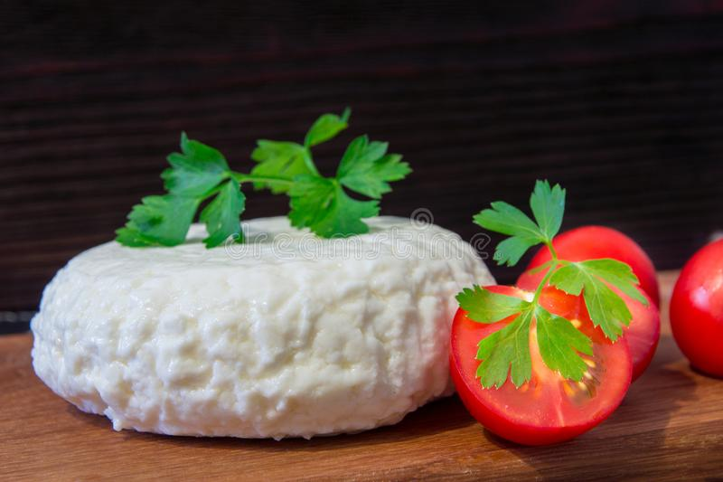 Young oak cheese cutting Board with tomatoes and parsley. Mozarella for pizzas and salads. royalty free stock images