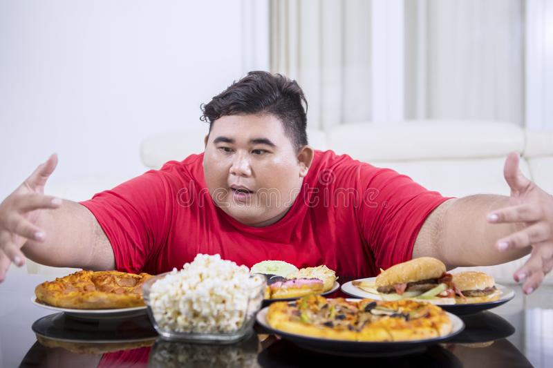 Young obese man looks tempted to eat lots of food. Picture of young obese man looks tempted to eat lots of unhealthy food at home stock photography