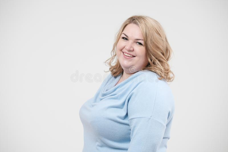 Young obese woman in casual blue clothes on a white background in the studio. Bodypositive. Young obese woman in casual blue clothes on a white background in royalty free stock images