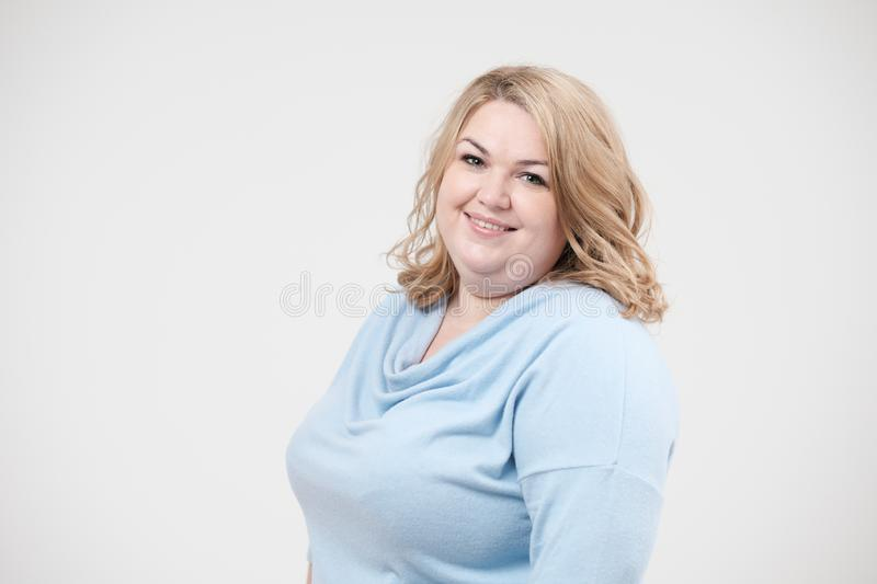 Young obese woman in casual blue clothes on a white background in the studio. Bodypositive. Young obese woman in casual blue clothes on a white background in royalty free stock photo