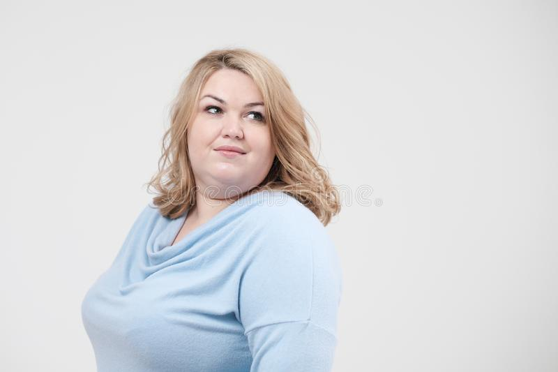 Young obese woman in casual blue clothes on a white background in the studio. Bodypositive. Young obese woman in casual blue clothes on a white background in stock image