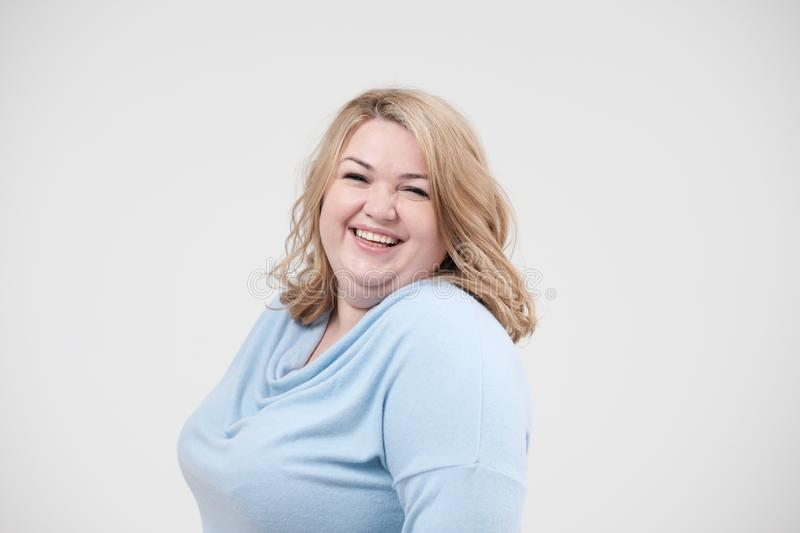 Young obese woman in casual blue clothes on a white background in the studio. Bodypositive. Young obese woman in casual blue clothes on a white background in royalty free stock image