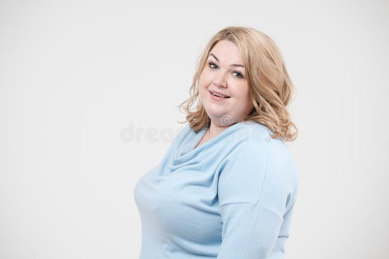 Young obese woman in casual blue clothes on a white background in the studio. Bodypositive. Young obese woman in casual blue clothes on a white background in stock photos