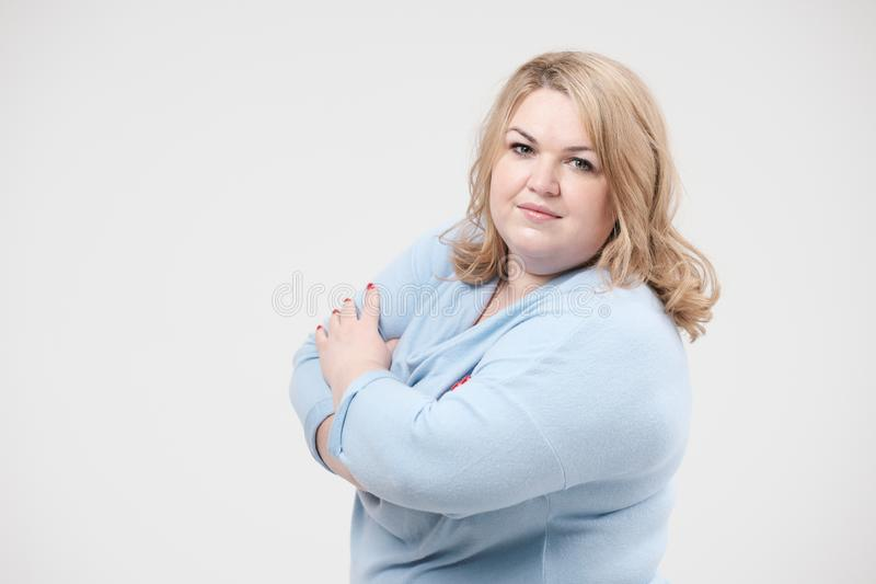 Young obese woman in casual blue clothes on a white background in the studio. Bodypositive. stock photos