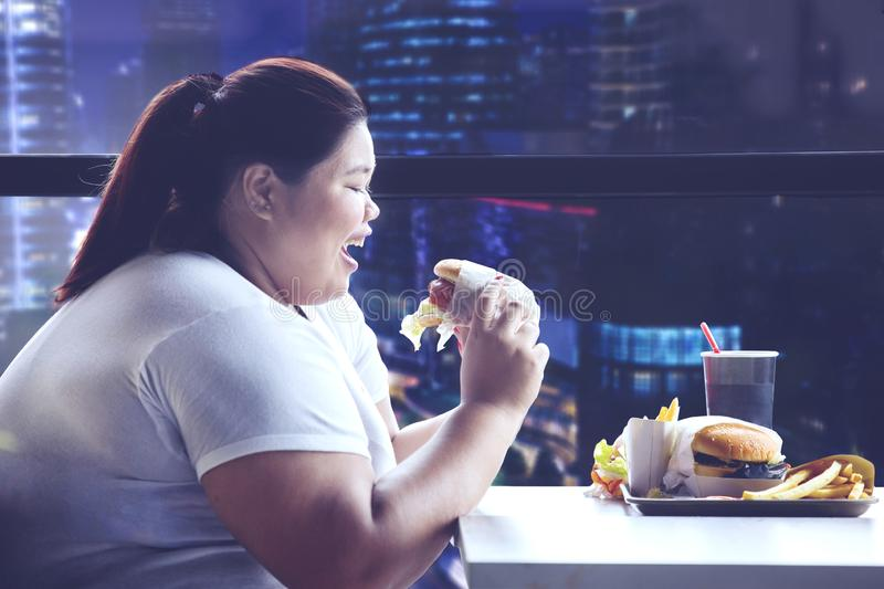 Young obese woman having dinner with junk food stock images