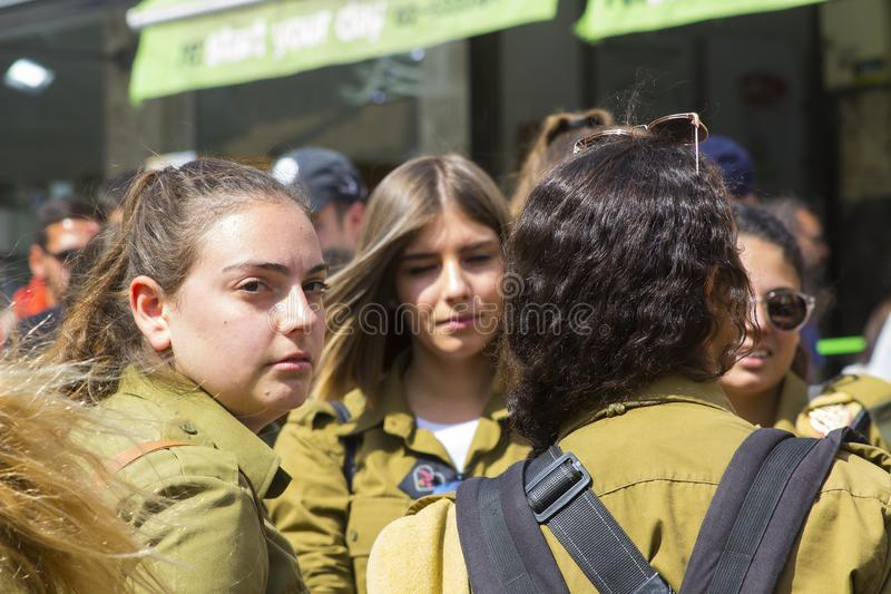 A young off duty female Israeli Army conscript looks way from her group wistfully as they relax together at the Mahane Yehuda stre stock photography