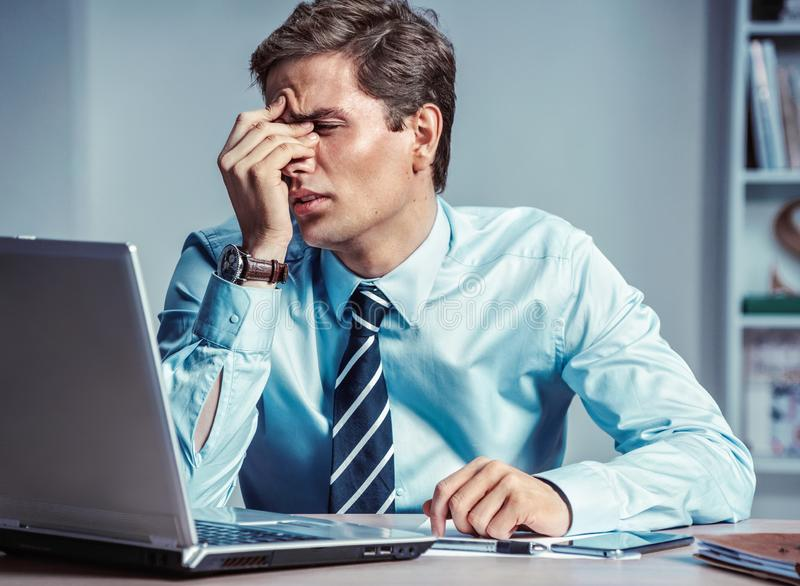 Young office man with pain in his head or an eye. stock photography