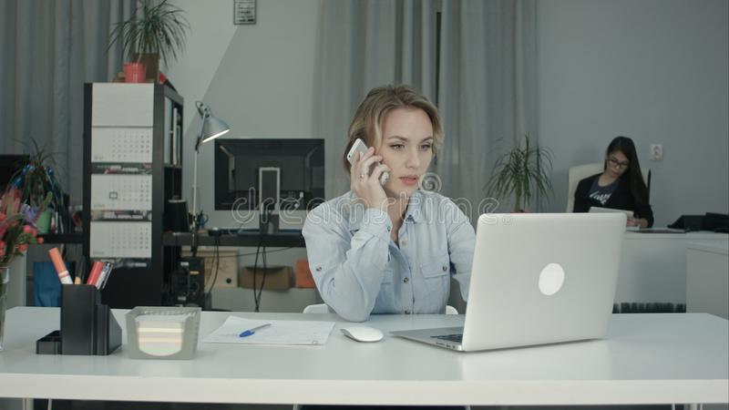 Young office secretary working on laptop and answering phone call royalty free stock photography