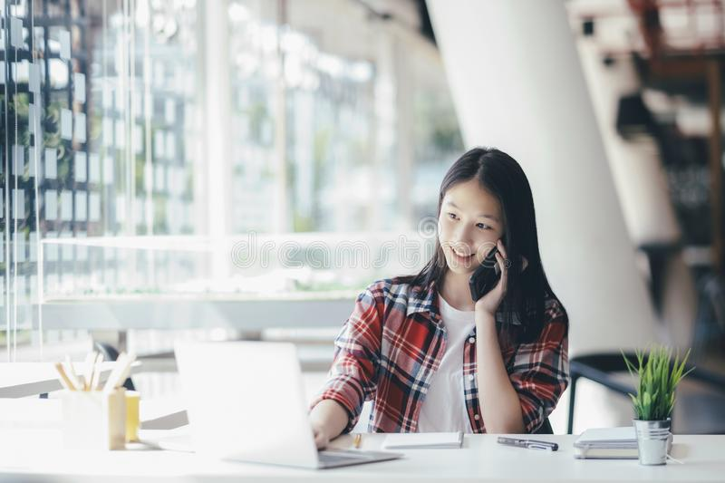 Young office woman talking on mobile phone with client. Young office woman talking on mobile phone. Young startup businesswoman using her cell phone and talking royalty free stock photography