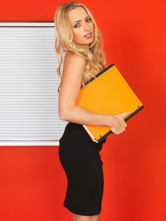 Young Office Worker Holding Businness Files. Attractive Young business Woman with long blonde hair in her twenties, Holding an orange coloured Business File royalty free stock photo