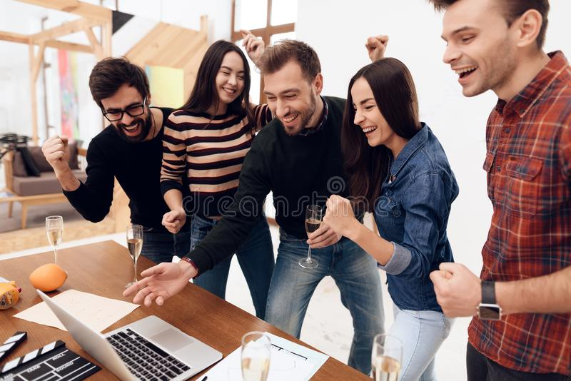 Young office workers looking at laptop screen together. They have glasses with champagne in their hands. They are in a good mood royalty free stock photos