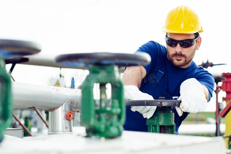 Oil worker turning valve on oil rig. Young Oil worker turning valve on oil rig royalty free stock photo