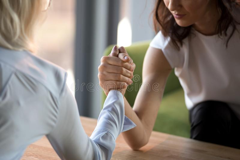Young and old businesswomen compete arm wrestling fighting for leadership. Feeling jealous envious about other success, female rivals armwrestling struggling royalty free stock photo