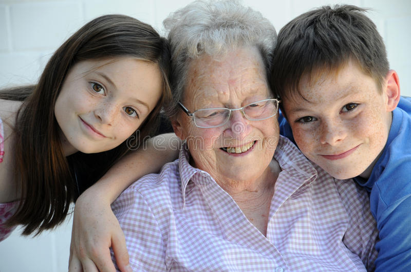 Young and old. Grandchildren embracing their ninety years old grandmother