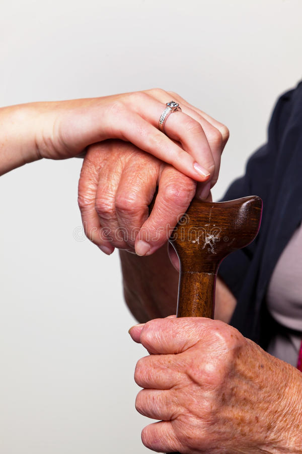 Young and old hand with a walking cane royalty free stock images
