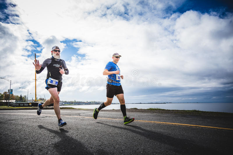 On young and old Man doing the full Marathon. CARLETON, CANADA - June 4, 2017. During the 5th Marathon of Carleton in Quebec, Canada. Two man doing the marathon royalty free stock images