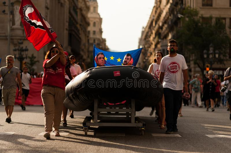 Barcelona, spain- 17 july 2019: young open arms activist march holding rubber dinghy and italian minister Salvini mask against stock photos