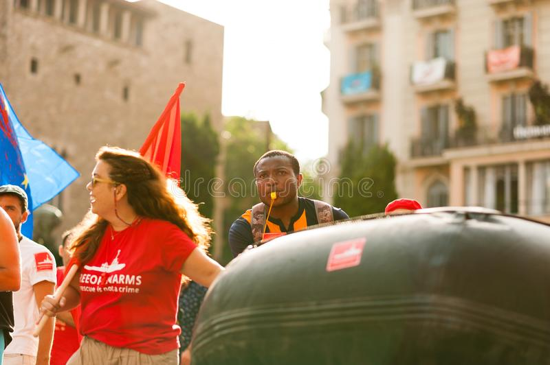 Barcelona, spain- 17 july 2019: young open arms african migrant march holding rubber dinghy and italian minister Salvini mask stock photography