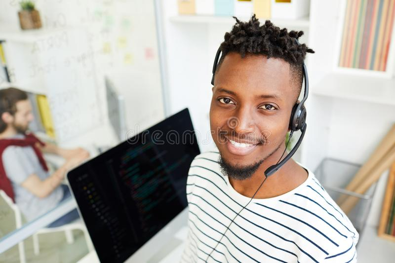 Young operator. Smiling young office manager in headset looking at you while communicating with clients stock photos