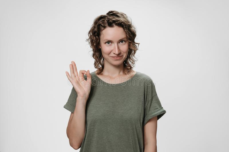 Young optimistic woman with curly hair demonstrates okay sign royalty free stock photography