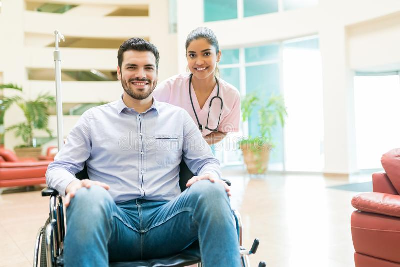 Young Orderly With Recovered Man At Hospital Lobby royalty free stock photography