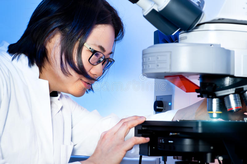 Download Young Oriental Scientist Tunes Her Microscope Stock Photo - Image: 27011486