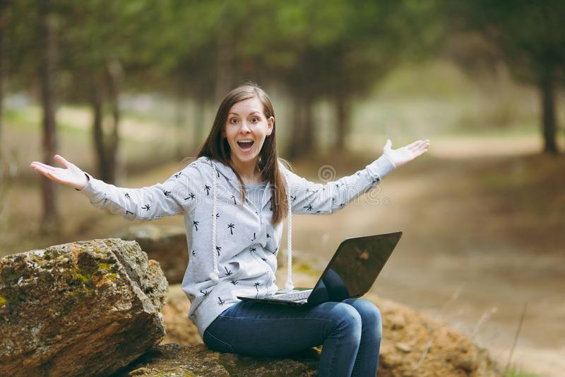 Young overjoyed smart business woman or student in casual clothes sitting on stone using laptop and spreading hands in royalty free stock photos
