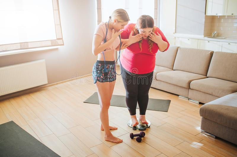 Young overweight and slim women in living room. Plus size model stand on weight scale. They look down. Daylight. Body royalty free stock photography