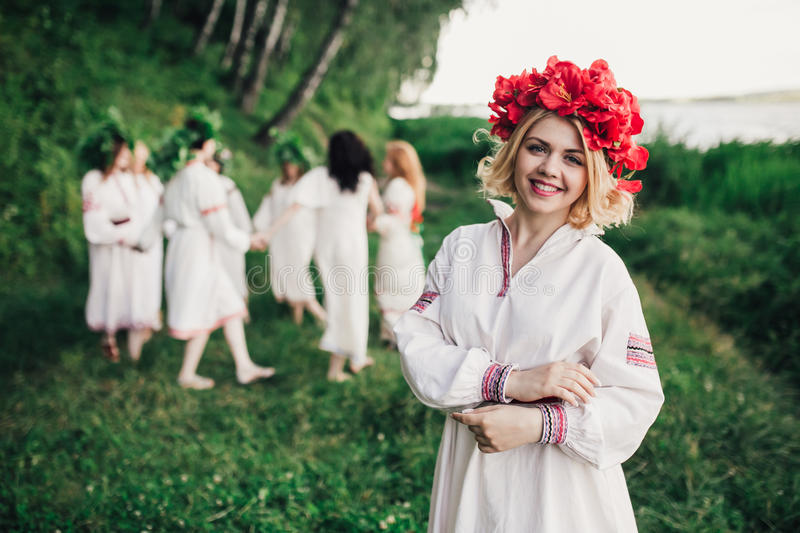 Young pagan Slavic girl conduct ceremony on Midsummer. Earth DayÑŽ Girls in the Ukrainian attire sitting against the backdrop of the river in wreaths of royalty free stock images