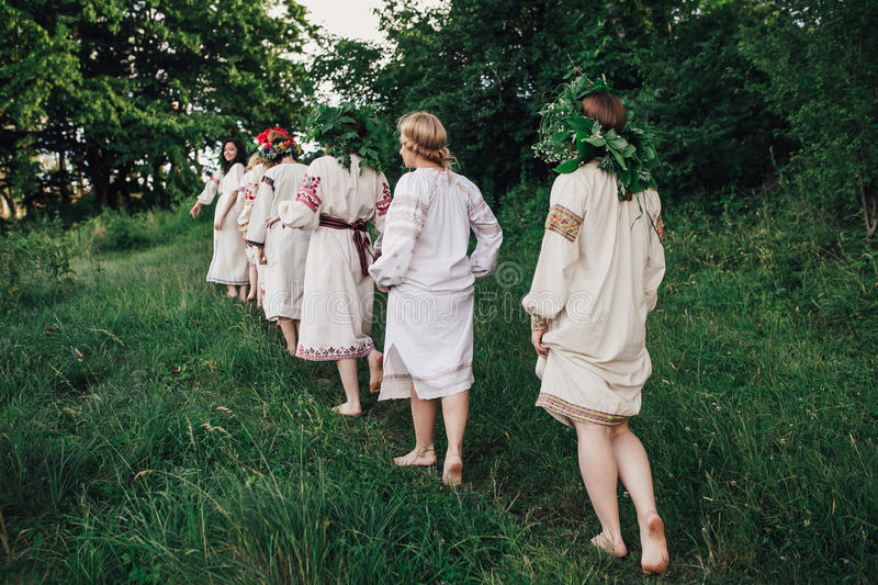 Young pagan Slavic girl conduct ceremony on Midsummer. Earth DayÑŽ Girls in the Ukrainian attire sitting against the backdrop of the river in wreaths of stock photo