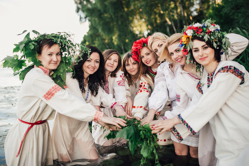 Young pagan Slavic girl conduct ceremony on Midsummer. Earth DayÑŽ Girls in the Ukrainian attire sitting against the backdrop of the river in wreaths of royalty free stock photography