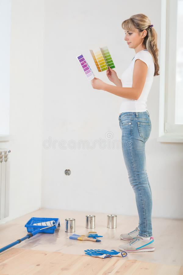 Young painter standing in room holding two color palettes and lo stock image