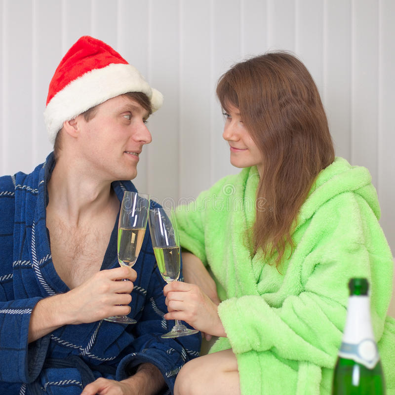 Young Pair Drinks Champagne Sitting On Sofa Royalty Free Stock Photography