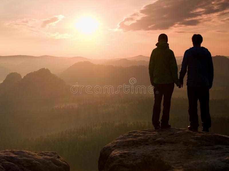 Young pair of hikers hand in hand on the peak of rock empires park and watch over the misty and foggy morning valley to Sun. Beaut. Young pair of hikers hand in stock image