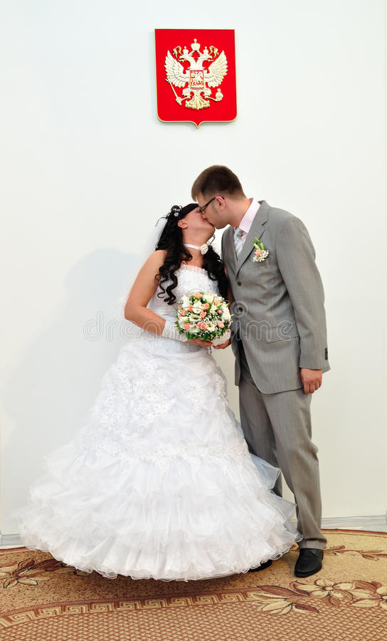 Young pair kisses in the registry office royalty free stock photo